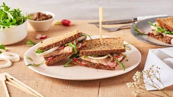 Sandwich au poulet, à l'aubergine, aux oignons, aux radis et à la roquette